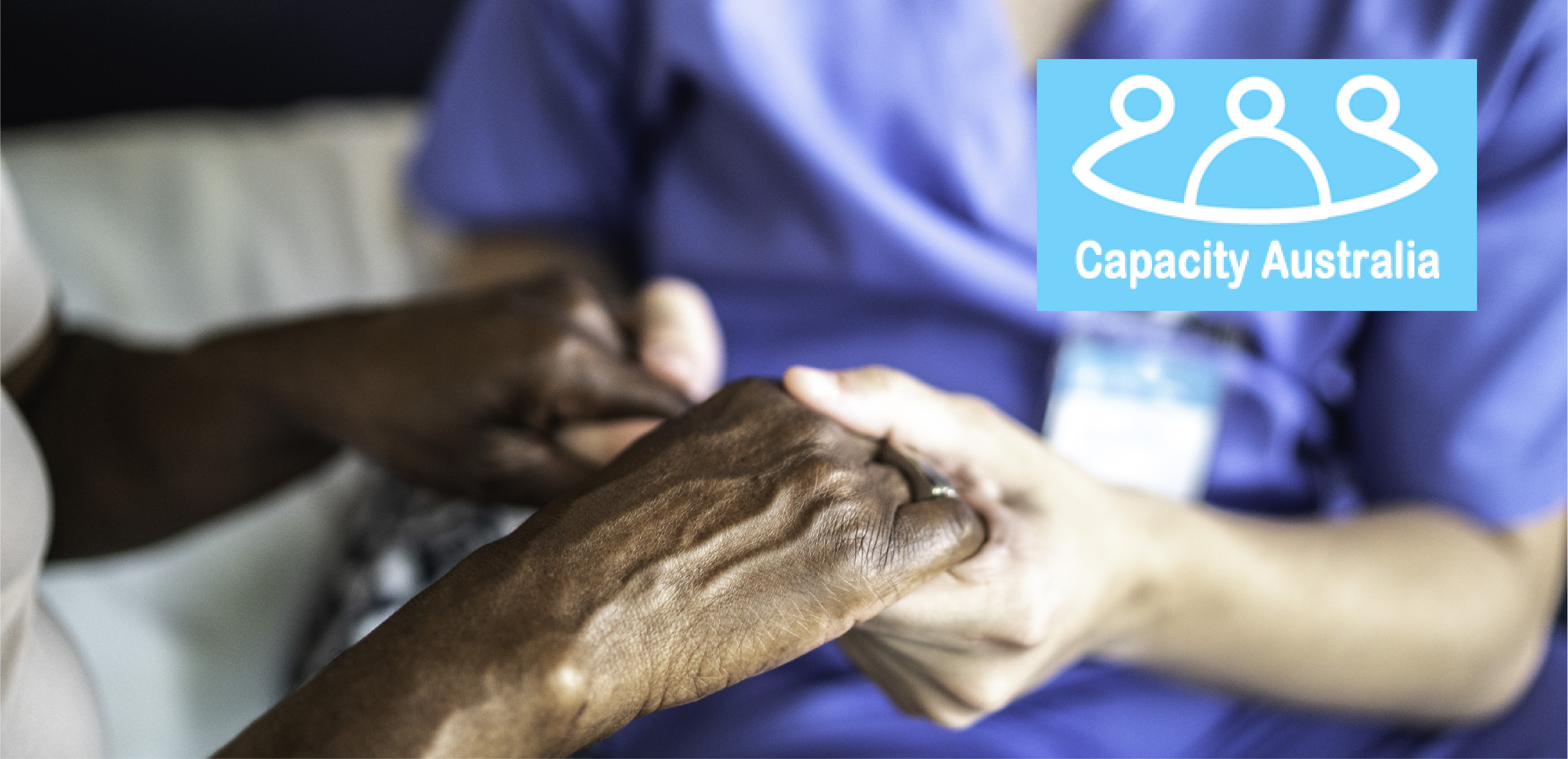 Capacity Australia logo over picture of nurse holding woman's hands