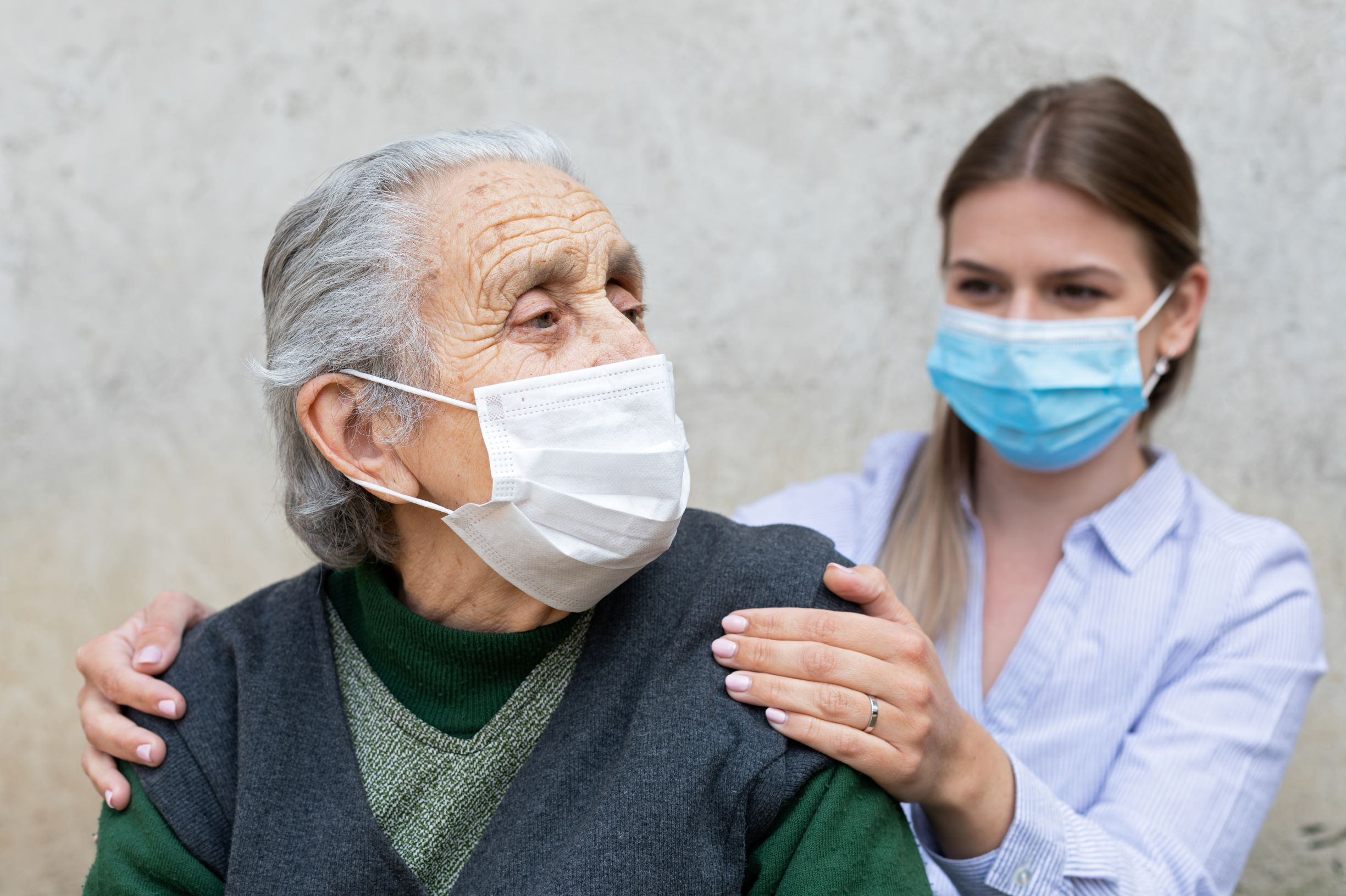 young woman cares for an older woman both wear face masks
