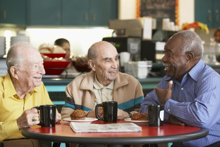 three men chat around a table in a coffee shop