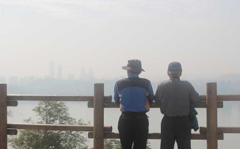 two men look out at air pollution over a city