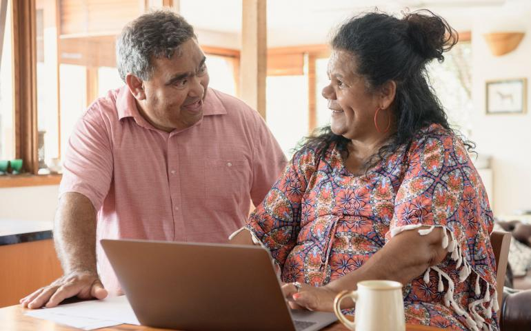An Aboriginal couple chatting and smiling, the woman is using a laptop