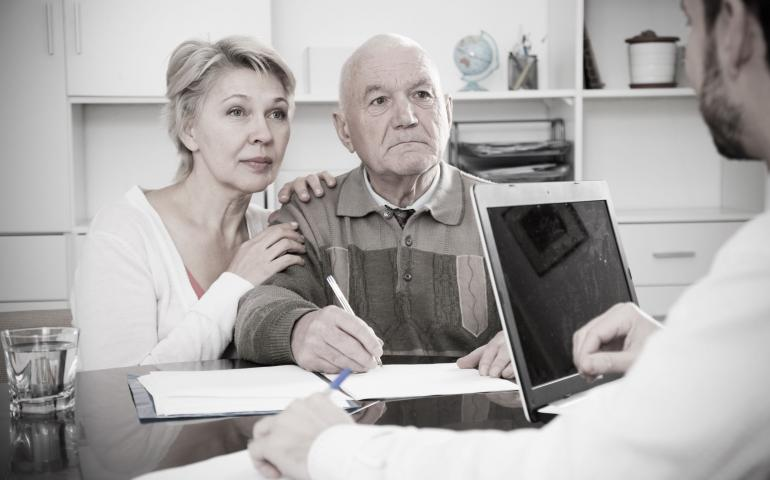An older couple consult a health professional