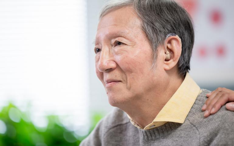 asian man with hearing aid, person's hand on his shoulder